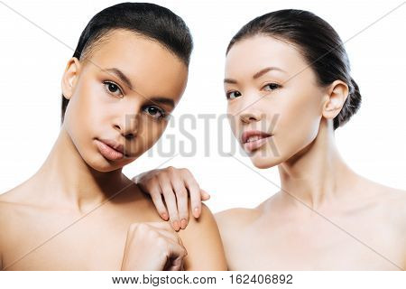 We enjoying modeling. Involved graceful passionate girls standing close to each other and expressing elegance while being isolated in white background