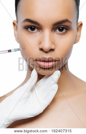 My appearance transformation. Decisive motionless young Negroid woman standing isolate in white background and expressing strength while getting the injection in her face