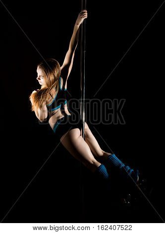 Hot young woman in sexy lingerie performs sensual pole dance. Go-go dancer.
