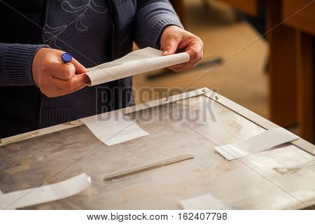 A person casts her ballot during voting for parliamentary elections at a polling station in Bucharest Romania.