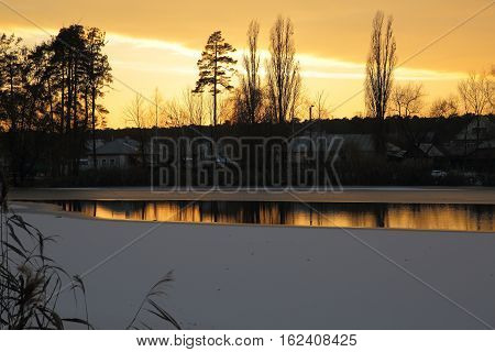 Already gone behind the horizon the sun brightly lit the sky and reflected in the unfrozen water