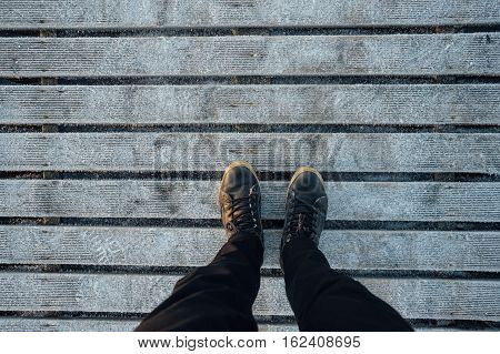 Male legs in leather boots standing on frozen wooden planks floor top view