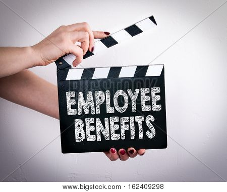 Employee Benefits. Female hands holding movie clapper.