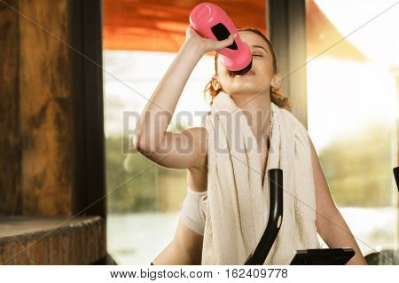 Active Young Woman Doing Exercise On Bicycle At Home. Woman Drinking Power Drink