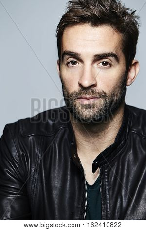 Leather wearing dude looking at camera studio