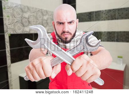 Angry Plumber Holding Crossed Wrenches