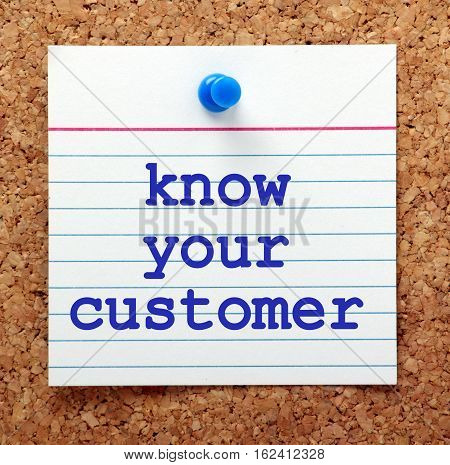 The words Know Your Customer on a note card pinned to a cork notice board as a reminder to research your market in business