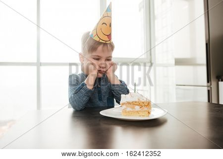 Photo of sad birthday boy sitting in kitchen near cake alone. Look at cake.