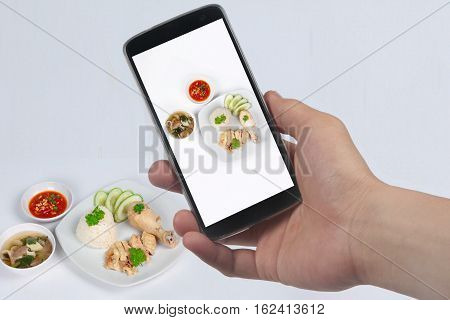 Use Phone to take photo a dish of Hainanese chicken rice streamed oily rice and streamed chicken and deep fried chicken to share.