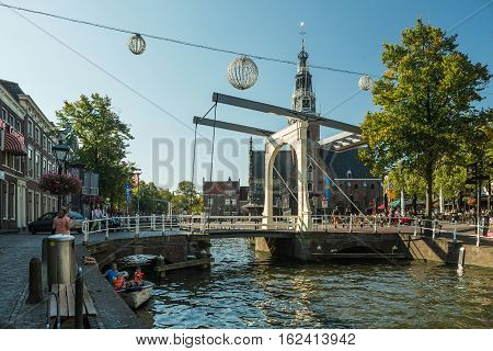ALKMAAR HOLLAND - SEPTEMBER 25 2016: View down a canal in the Old Town of Alkmaar towards the Weigh House Netherlands. The old drawbridge per channel