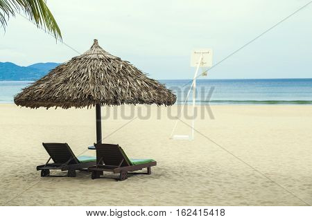 Straw Umbrella, Sunbed And Basketball Ring In Deserted Beach
