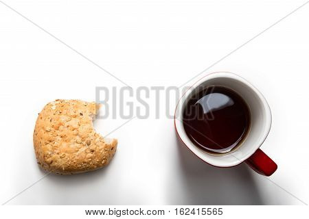 Beaten roll with grains and a mug of tea isolated on white
