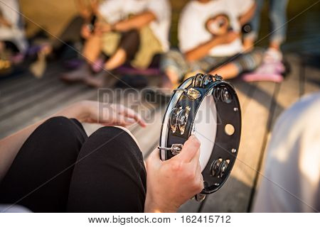 Someone holding a tambourine and trying to play