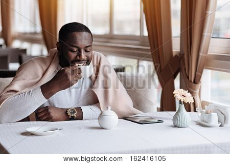 Delighted from my free time. Positive happy sincere African American man sitting in the cafe and being covered with a blanket while drinking the cup of tea