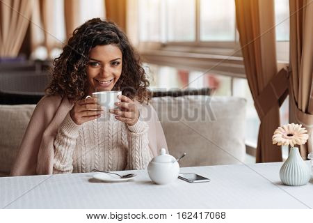 Delighted from a cozy place. Cheerful positive delighted African American woman sitting in the cafe and being covered with a blanket while drinking the cup of tea and smiling