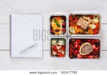 Healthy restaurant food delivery, diet plan. Fresh daily meals. Fitness nutrition, vegetable, meat and fruits in foil boxes and notepad, empty sheet with copy space. Top view, flat lay on white wood