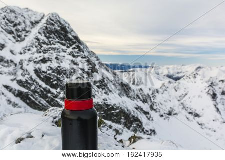 Red And Black Thermos In The Mountains.