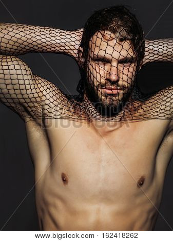 Young handsome man bearded guy with beard or robber bandit gangster wears mask of black fishnet stocking on face on dark background with bare muscular chest