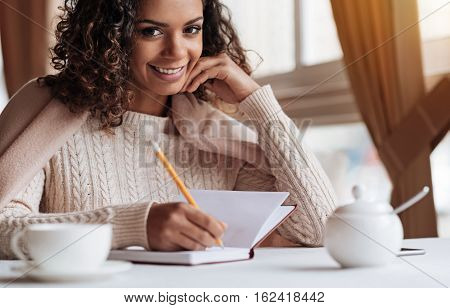 Happy from a process of writing. Smiling positive delighted African American woman sitting in the cafe and being covered with a blanket while making notes in the notebook poster