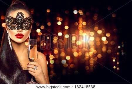 Beauty Glamour Woman celebrating with champagne, wearing carnival mask. party, drinking champagne over holiday glowing background. Christmas and New Year celebration.
