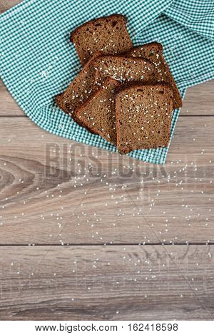 Freshly baked delicious wholewheat bread served on black and read cloth and wooden tray for some meal.