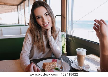 Woman sitting by the table with food on date in cafe near the sea, looking at camera and holding hand her man. First-person view