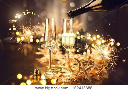 Christmas and New Year celebration with champagne. New Year holiday decorated table. Two Champagne Glasses, vintage toned