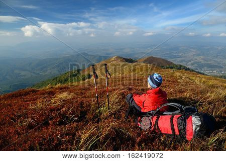Tourist halt in mountains. Woman has bright red outdoorsy clothing and backpack. Sky and mountain ranges in background. Red bilberry leaves in foreground.