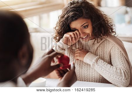 The feeling of happiness. Surprised affected cheerful African American woman sitting in the cafe while expressing tenderness and receiving the engagement ring from her boyfriend