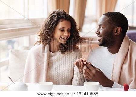 Happiest woman in the world. Smiling cheerful positive African American couple sitting in the cafe and being covered with a blanket while getting engaged and expressing happiness