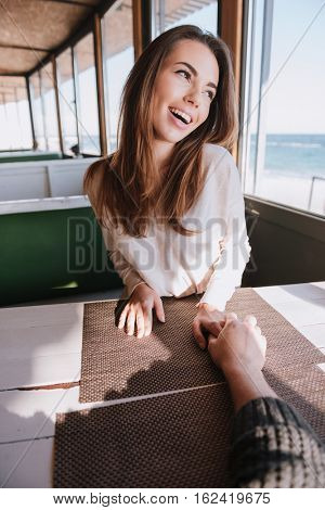 Vertical image of laughing woman on date sitting by the table in cafe near the sea, looking away and holding hand her man. First-person view