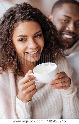 Delightful from being in love. Smiling cheerful positive African American couple sitting in the cafe and being covered with a blanket while expressing love and drinking tea