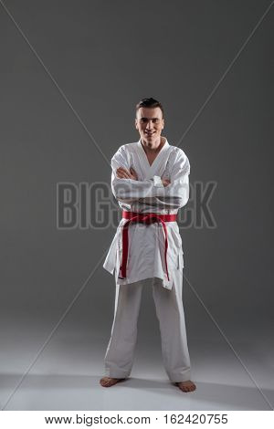 Photo of attractive young sportsman in kimono practice in karate and posing. Look at camera.