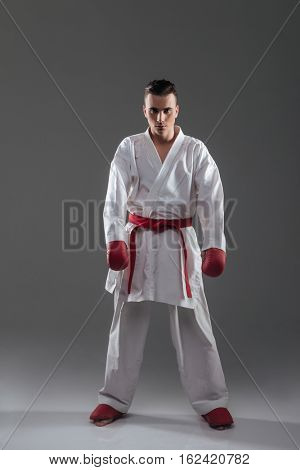 Picture of handsome young sportsman in kimono practice in karate and posing. Look at camera.