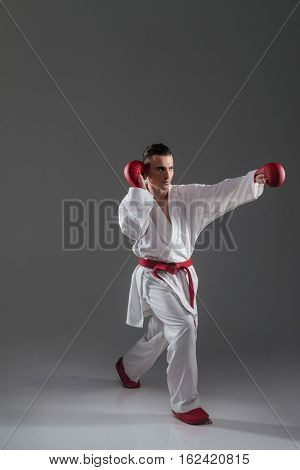 Handsome young sportsman in kimono practice in karate isolated over grey background. Look aside.