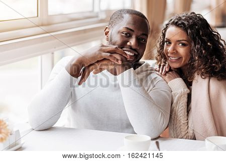 Positive atmosphere around us . Charming positive smiling African American couple having the date in the cafe and being covered with a blanket while expressing happiness and love