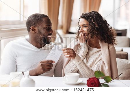 Long awaited surprise. Cheerful delighted surprised African American woman sitting in the cafe with her boyfriend and receiving the envelope from him while having the date and expressing amazement