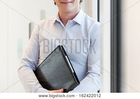 Portrait of smiling mature businesswoman holding file in office