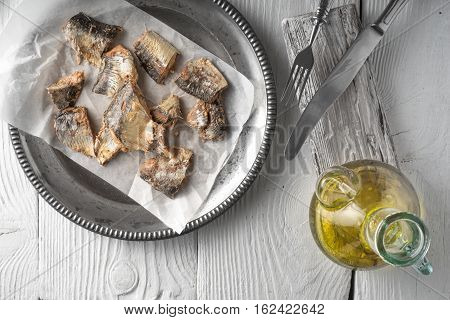 Plate with fish and olive oil on a wooden table horizontal