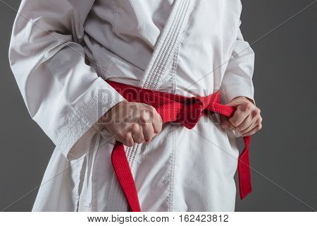 Cropped image of sportsman dressed in kimono practice in karate while tightening red belt isolated over grey background.