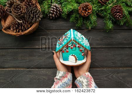 Christmas decoration. Woman's hands is holding a gingerbread house on wooden table.