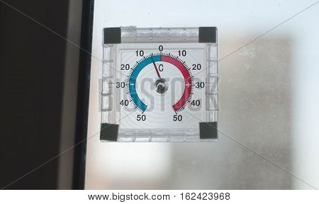 below zero on the old analogue thermometer, the concept of cold weather, the thermometer outside the window, frost on the yard