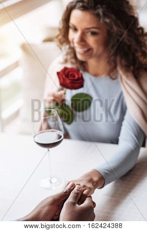 With my soulmate. Charming embarrassed smiling African American woman sitting in the restaurant and looking at her boyfriend while expressing affection and holding hands poster