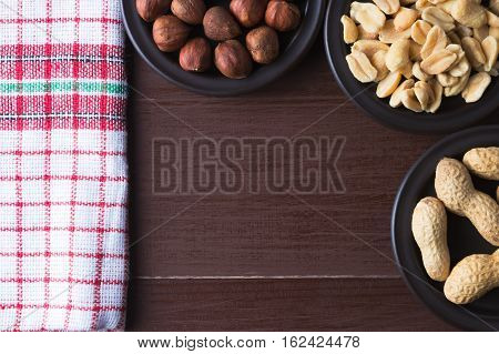 Hazelnuts and peanuts on a dark plates. Brown natural table and vintage kitchen dishcloth. Flat lay top view. Copy space on the bottom. Vegetarian food concept.