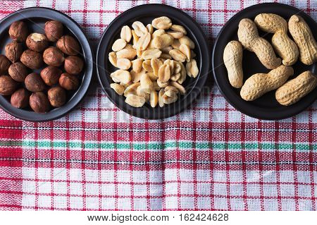 Hazelnuts and peanuts on a dark plates. Vintage kitchen dishcloth. Flat lay top view. Copy space on the bottom. Vegetarian food concept.