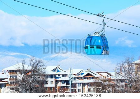 Ski resort Bansko, Bulgaria panorama with cable car ski lift cabin, snow mountains and houses in winter