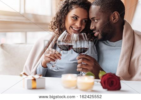 Crazy for you. Passionate positive cheerful African American couple sitting in the restaurant and hugging each other while being covered with the blanket and drinking wine