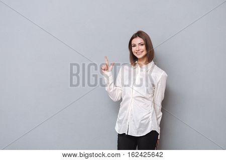Portrait of a smiling girl in shirt pointing finger up and looking at camera over white background