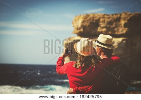 Tourist couple making selfie photo on Azure Window in Gozo island, Malta