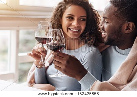 The day with my sweetheart. Infatuated smiling delighted African American couple sitting in the restaurant and hugging each other while being covered with the blanket and drinking wine